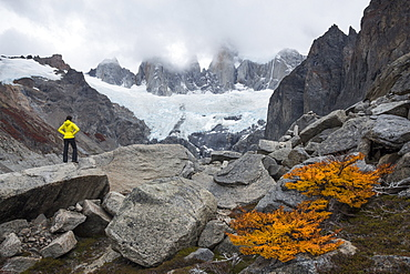 Female hiker with a hand-on-hip pose standing confident on a boulder and looking towards high peaks shrouded in clouds and a glacier below them