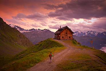A hiker is almost at the Cabane du Mont Fort, a mountain hut near Verbier. The sunset puts the sky in pink and purple colors. It rained all day, and cleared just before this picture. The hut is one of the places hikers stay at during the Haute Route, a classic hike between Chamonix in France and Zermatt in Switzerland.