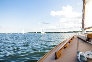 Classic wooden catboats sailing on Narragansett Bay during a summer afternoon