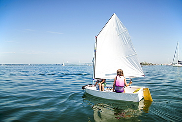 Young kids sailing a dinghy in Newport Harbor