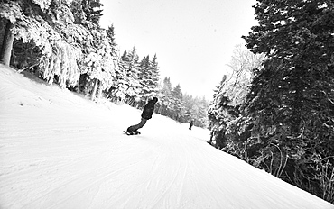 A snowboarder riding down a trail at Killington, VT.
