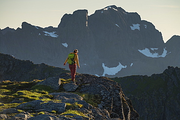 Female hiker on summit of Veinestind, Moskenesøy, Lofoten Islands, Norway