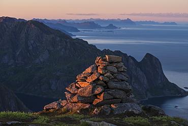 Summit cairn on Veinestind lit by setting sun, Moskenesøy, Lofoten Islands, Norway