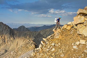 A man negotiating the ridgeline along the Evolution Traverse, John Muir Wilderness, Kings Canyon National Park, Bishop, California.