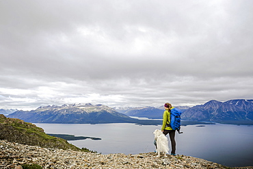 Female hiker with dog on Monarch Mountain overlooking Atlin Lake towards the Boundary Mountain Ranges British Columbia