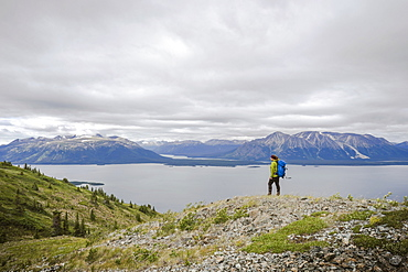 Female hiker on Monarch Mountain overlooking Atlin Lake towards the Boundary Mountain Ranges British Columbia