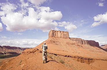 Male hiker nears Parriott Mesa in Castle Valley near Moab, Utah