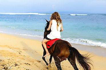 Young woman riding horse on beach