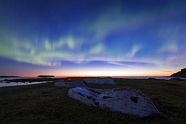 The Northern Lights over old wooden boats in the Norstead Viking replica village in Newfoundland.