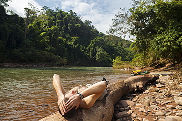 Robert Hahn rests on a sunny log on the shore of the Nam Ou RIver, Laos.