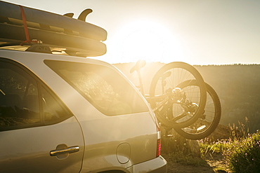 Vehicle loaded with mountain bikes and Stand Up Paddle Boards at sunset
