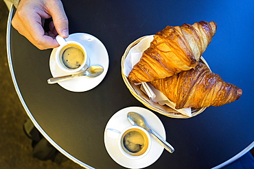 Espresso and Croissants in a basket on a table at a brasserie in Saint Michel, Paris, France