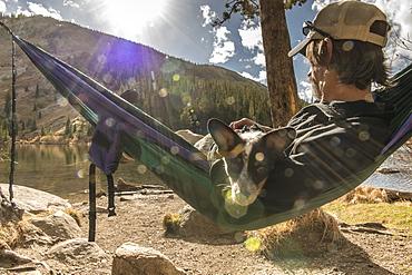 Man & dog in hammock by mountian lake