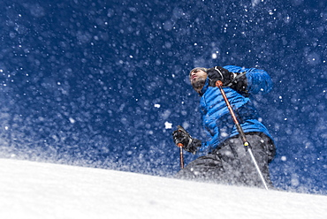 A low angle shot of a man snowshoeing with ski poles in the blowing snow.
