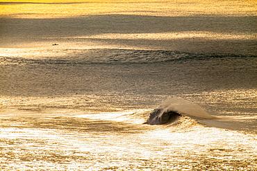 A huge wave off the lower north shore of Oahu, under golden Vog skies.