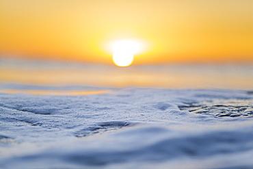 Macro focusing on the ocean, during sunrise.