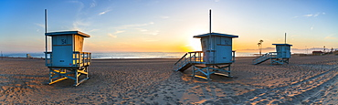 Deserted lifeguard stands at Dockweiler beach, in Los Angeles, during a golden sunset.