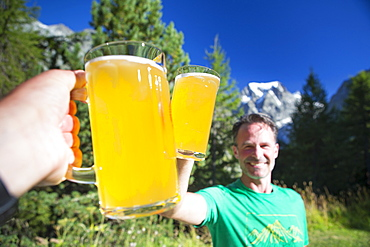 Two hikers are cheering with big local beers in the garden of the Arolla Kurhaus in the Swiss Alps. It is one of the places you can stay for the night half way the Haute Route, a classic multi day hike between Chamonix in France and Zermatt in Switzerland.