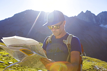 A male hiker is looking at a map to find his route through the mountains. Halfway the Haute Route, a classic multi day trek in Europe.