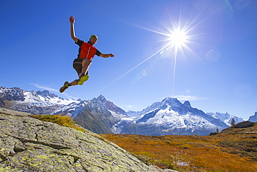 A young male runner is  jumping in the air on a mountain ridge near Chamonix with the spectacular Mont Blanc range in the background.