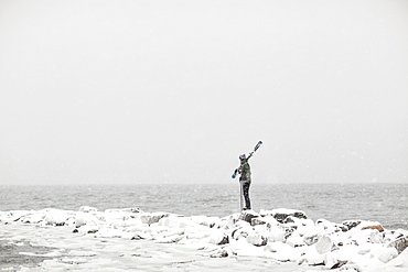 A lone skier stands and looks out at the stormy Atlantic Ocean in Portland, Maine.
