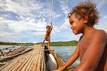 Children playing with a outrigger canoe in the village of Hessessai Bay at PanaTinai (Panatinane)island in the Louisiade Archipelago in Milne Bay Province, Papua New Guinea.  The island has an area of 78 km2. The Louisiade Archipelago is a string of ten larger volcanic islands frequently fringed by coral reefs, and 90 smaller coral islands located 200 km southeast of New Guinea, stretching over more than 160 km and spread over an ocean area of 26,000 km? between the Solomon Sea to the north and the Coral Sea to the south. The aggregate land area of the islands is about 1,790 km? (690 square miles), with Vanatinai (formerly Sudest or Tagula as named by European claimants on Western maps) being the largest. Sideia Island and Basilaki Island lie closest to New Guinea, while Misima, Vanatinai, and Rossel islands lie further east. The archipelago is divided into the Local Level Government (LLG) areas Louisiade Rural (western part, with Misima), and Yaleyamba (western part, with Rossell and Tagula islands. The LLG areas are part of Samarai-Murua District district of Milne Bay. The seat of the Louisiade Rural LLG is Bwagaoia on Misima Island, the population center of the archipelago.PanaTinai (Panatinane) is an island in the Louisiade Archipelago in Milne Bay Province, Papua New Guinea.