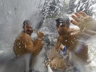 Two shirtless men taking selfie inside waterfall in Poco Verde (Green Pool), Guapimirim Sector in Serra dos Orgaos National Park, Rio de Janeiro, Brazil