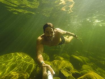 Shirtless man taking underwater selfie in Poco Verde (Green Pool), Guapimirim Sector of Serra dos Orgaos National Park, Rio de Janeiro, Brazil