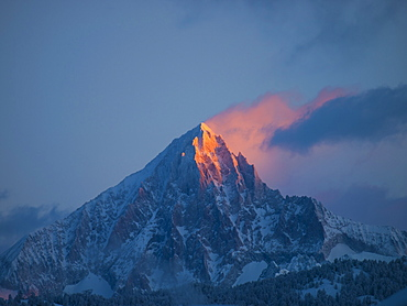 An early morning picture of the first sun rays setting the pyramid summit of the Bietschhorn mountain on fire.