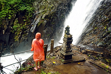 Rear view shot of woman in raincoat looking at waterfall, Kintamani, Bali, Indonesia