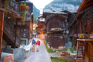 Narrow street with old wooden houses in historical part of Zermatt, Valais, Switzerland