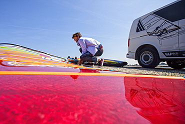 Pierre Le Coq preparing his windsurfing gear on a jetty near his van at Plouguerneau, Brittany, France.