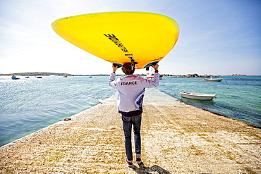 Pierre Le Coq carries his windsurfing board over his head on a jetty at Plouguerneau, Brittany, France.