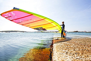 Pierre Le Coq carries his windsurfing board on a jetty at Plouguerneau, Brittany, France.