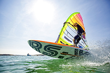 Pierre Le Coq performing a jibe with his windsurf board at Plouguerneau, Brittany, France.