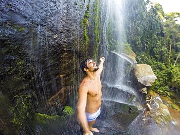 Man standing under waterfall with open arms, Guapiacu Ecological Reserve, Rio de Janeiro, Brazil