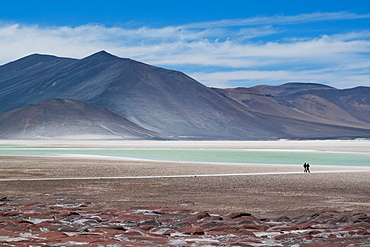 Silhouette of two people by lakes at Piedra Rojas on Altiplano in Atacama Desert, Chile