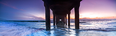 Panoramic sunset view from underneath of Manhattan Beach Pier, Los Angeles, California, USA