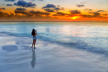Photograph of woman photographing Caribbean Sea on beach at sunset, Isla Mujeres, Yucatan Peninsula, Mexico