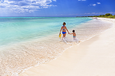 Rear view photograph with mother with daughter walking on beach of Caribbean Sea, Cozumel, Quintana Roo, Mexico