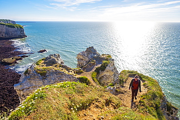 Young woman hiking on cliffs overlooking English Channel, Etretat, Normandy, France