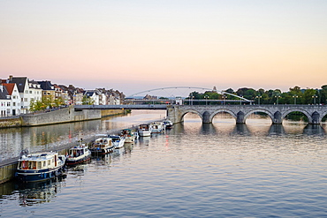 Photograph of Meuse River with bridge, boats and buildings on bank, Maastricht, Limburg, Netherlands