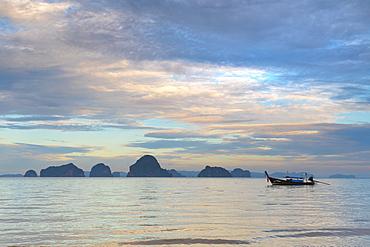 View of long tail boat floating on Adaman Sea at sunrise, Krabi, Krabi Province, Thailand