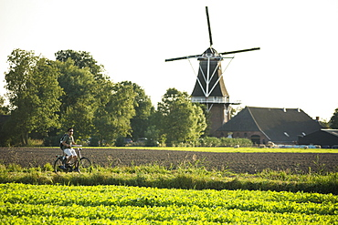 A young man wearing shorts, a green t-shirt and sunglasses, rides his bike on a sunny day, in the Dutch countryside, with a windmill in the background, in the province of Groningen, in The Netherlands.