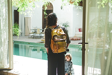 Photograph with mother with son standing by swimming pool in Moroccan riad, Marrakech, Morocco