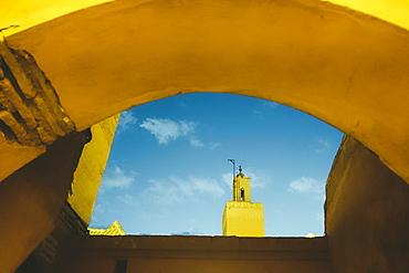 Photograph with Koutoubia Mosque minaret seen through arch, Medina, Marrakech, Morocco