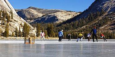 People playing ice hockey on a frozen, snow free Tenaya Lake in Yosemite National Park.