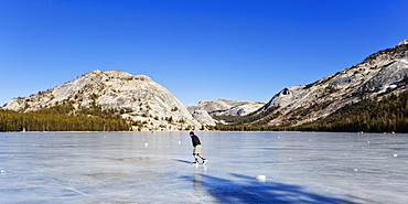 A lone man ice skating on a frozen lake.