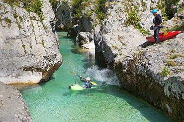 A man in a kayak is jumping into the water, while another man is watching. The emerald Soca near Bovec in Slovenia, originating in the Triglav mountains, is famous for all kinds of white water activities.