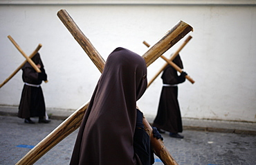 Hooded penitents carry crosses during Easter Week celebrations in Baeza, Jaen Province, Andalusia, Spain